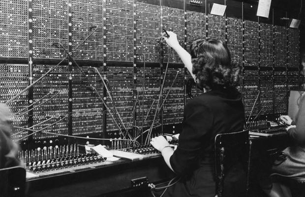An operator plugging cables in an very big switchboard